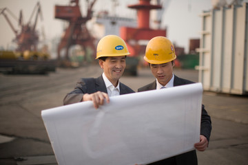 Young adult businessman standing looking at plans with a mid-adult colleague on a shipping dock.