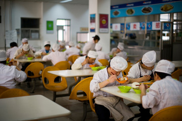 Kitchen staff eating food in a canteen.