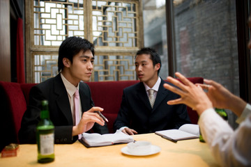 Young adult businessmen sitting at a table in a bar drinking beers and smoking.