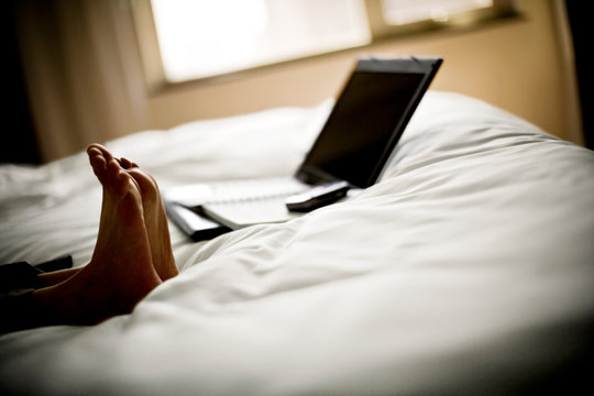 Feet on a bed with a laptop.