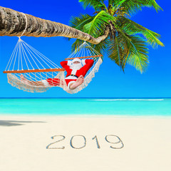 Santa Claus relax in hammock under palm tree at island tropical beach with handwritten caption 2019 happy new year