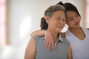 Teenage girl hugging her senior grandmother in a yoga studio.