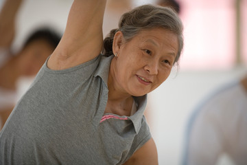 Senior adult woman doing yoga poses with a group of women  in a class.