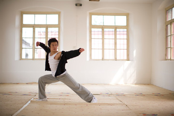 Teenage boy standing in a martial arts pose in a room.