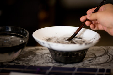 Paintbrush being dipped into a bowl.