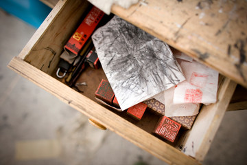 Stamps and a sketch sitting in a wooden draw.