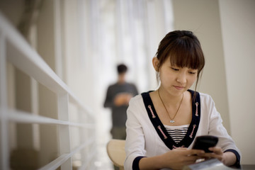 Teenage girl texting while in a study hall.