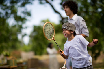 Young boy and his older brother playing badminton