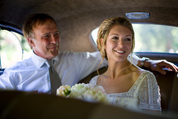 Young adult bride holding flowers in a car with her mature father on her wedding day.