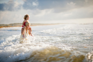 Smiling mother and daughter playing in the surf.