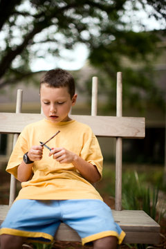 Young boy shaping a twig with a pocketknife.