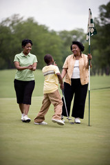 Boy playing golf with Mother and Grandmother