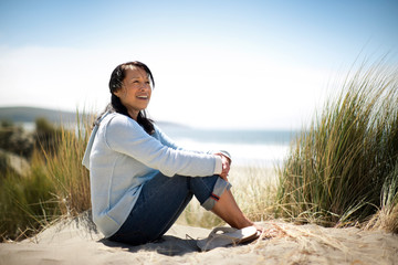 Smiling middle aged woman sitting on sand dunes at the beach.