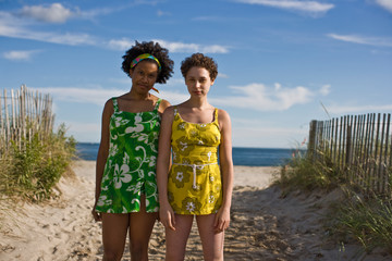 Young women standing side by side on the beach