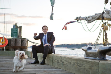 Suited businessman smiling while watching his small white dog run along a wooden wharf.