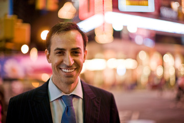 Portrait of a smiling mid-adult businessman at night with city lights behind him.