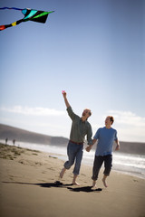 Homosexual male couple flying a kite while holding hands on a beach.