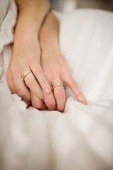 Matching wedding bands on the hands of a couple.