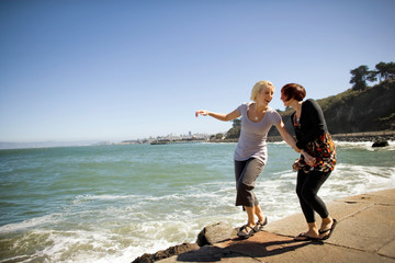 Two young women having fun together on a footpath next to a beach.