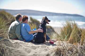 Happy male couple at the beach with their dog.