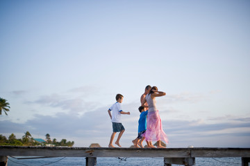 Couple and their sons walking along a jetty over water.