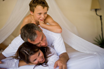Boy lying on top of a mid-adult couple on a bed.