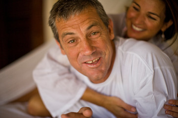 Portrait of a mid-adult man being hugged by his wife on a bed.