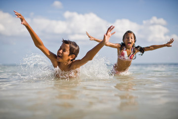 Boy and his younger sister having fun swimming in the water at the beach.