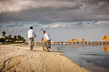 Portrait of a smiling mid-adult man waving while riding a bicycle with his son on a sandy beach near the water.
