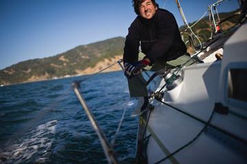 Mid-adult man sitting on a sail boat at sea.
