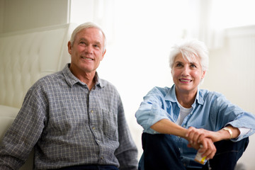 Mature adult couple reading the label of medicine while sitting on the floor.