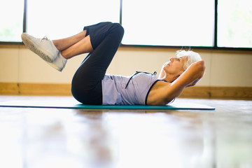 Mature adult woman doing crunches at a gym.