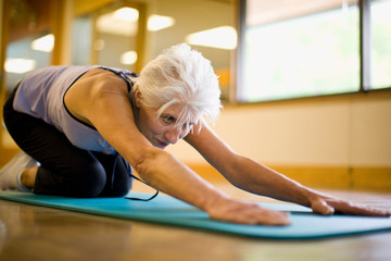 Mature adult woman stretching her lower back at a gym.
