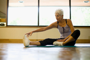 Mature woman stretching her inner thigh while at a gym.