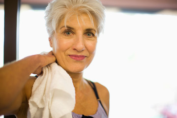 Portrait of a mature adult woman holding a sweat towel at a gym