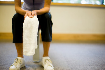 Towel held by a mature woman inside a gym.