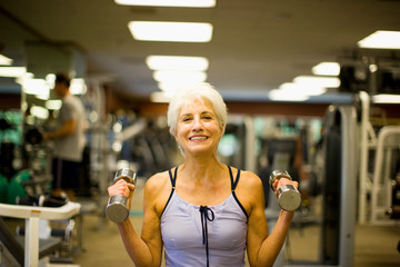 Smiling mature woman working out at the gym.