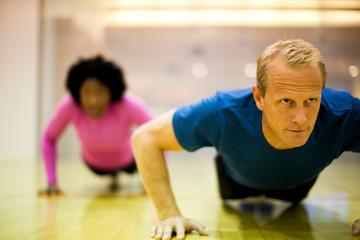 Mid-adult man doing press ups inside a gym.