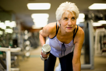 Active senior woman lifting hand weights inside a gym.