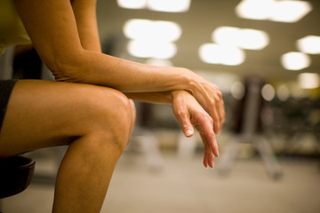Women's hands and legs resting in a gym.