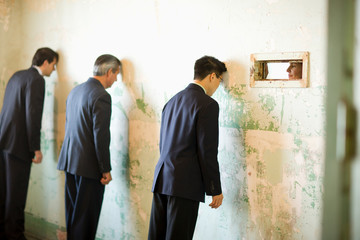 Three businessmen leaning on a wall with their heads while a mid-adult female colleague looks at them through a hole in the wall in a derelict building.