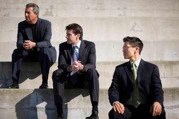 Three businessmen sitting on steps while outside a building.