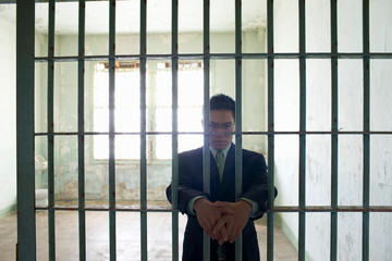 Portrait of a confident young businessman standing in a empty prison cell behind bars in a derelict building.