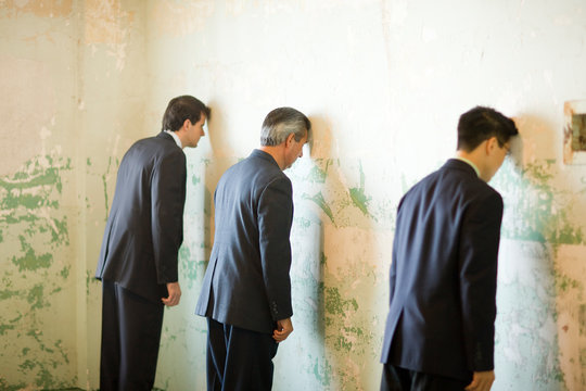 Three businessmen leaning on a wall with their heads in a derelict building.