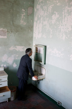 Mature adult businessman leaning on a sink while looking in an old cabinet in a derelict building.