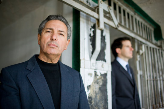 Portrait of a mature businessman standing beside a cell in a derelict building.