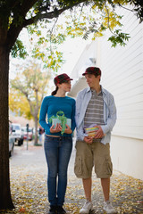 Teenage couple standing side by side with gifts