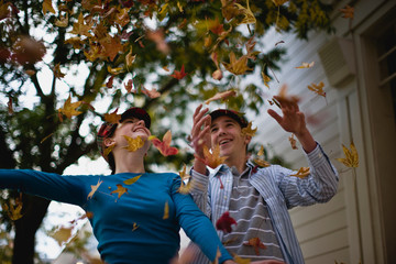 Teenage couple plays amongst autumn leaves