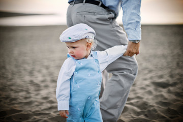 Young toddler wearing a flat cap while holding hands and walking along a sandy beach.