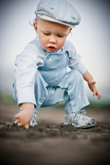 Young toddler wearing a flat cap and blue overalls while crouching and drawing in the sand with his finger on a beach.